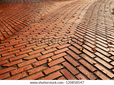 Red brick road split into two directions with herringbone pattern requiring a decision