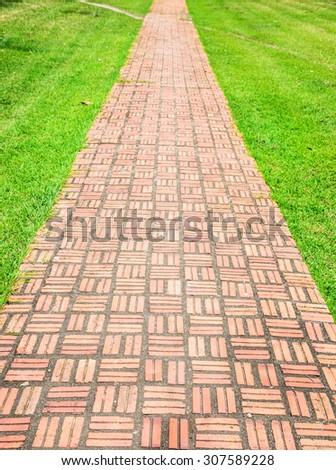 Red brick walk path on green grass. - stock photo