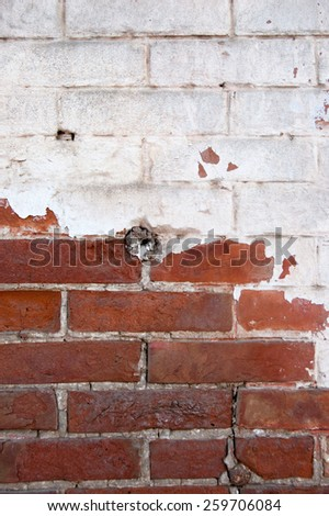 Red brick wall half painted in white vertical image. - stock photo