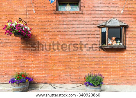 red brick wall texture background with window display and flower. - stock photo