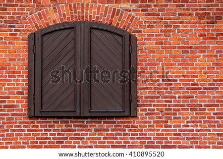 Red brick wall with a closed window with shutters - stock photo