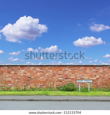 Red Brick Wall with a Main Street Sign and Sidewalk - stock photo