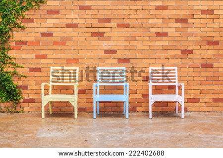 Red brick wall with chairs and ornamental - stock photo