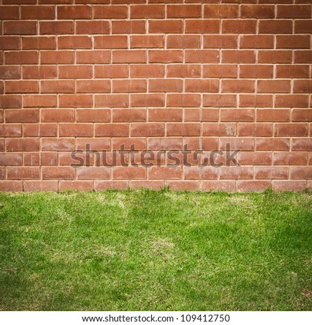 Red brick wall with grass floor - stock photo