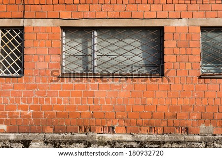 Red brick wall with metal window bars - stock photo