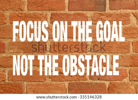 red brick wall with quote - focus on the goal not the obstacle - stock photo