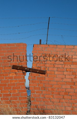 Red brick wall with rusty barbed wire - stock photo