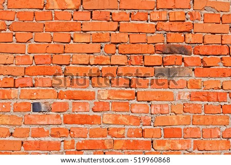 Red brick wall with several over burned black bricks in bright sunlight