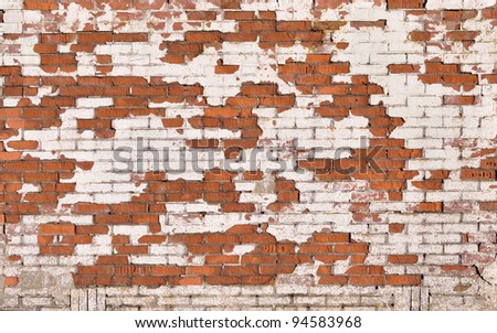 Red brick wall with severe damaged white stucco - stock photo