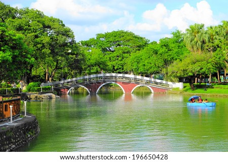 red bridge and green lake at Taichung Park - stock photo