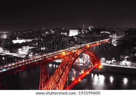 Red Bridge on a monochromatic background, night view of the Dom Luiz bridge captured on a slow shutter, Porto , Portugal - stock photo