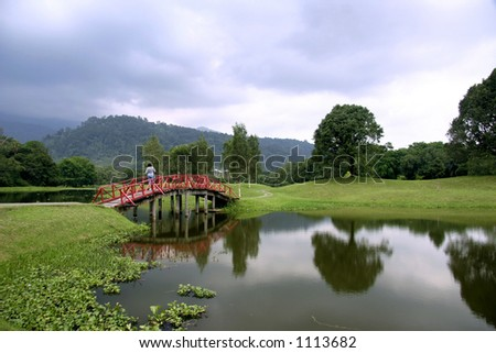 Red bridge over calm waters at the Taiping Lake Gardens - stock photo