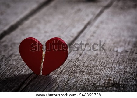 red broken heart on wooden background - dark and moody