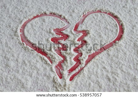 Red broken heart pictured on white flour background