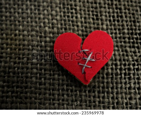 Red broken heart stitched with thread on textured background                               - stock photo