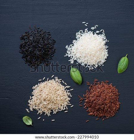 Red, brown, white and black rice over black wooden background - stock photo