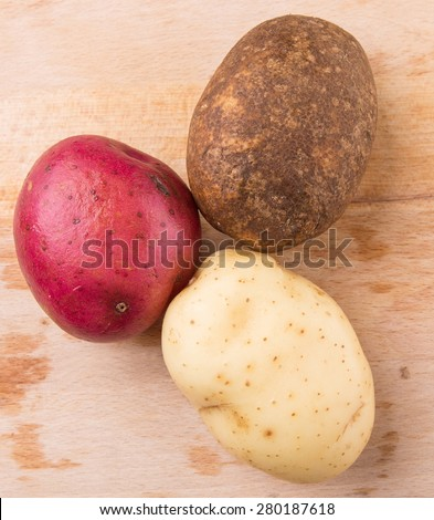 Red, brown, yellow potatoes on wooden surface - stock photo