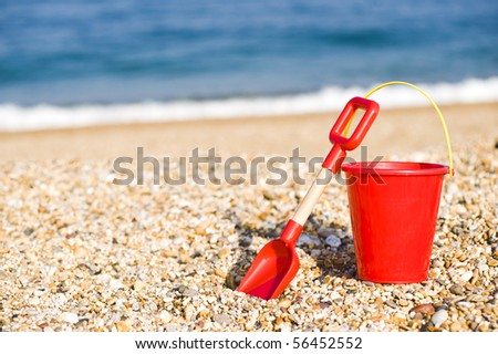 Red Bucket And Spade Lying On A Beach