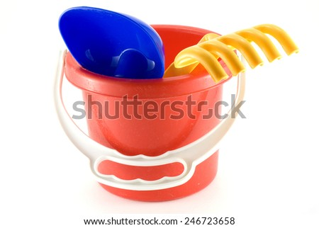 Red bucket toy with yellow rake and blue shovel isolated on white background - stock photo