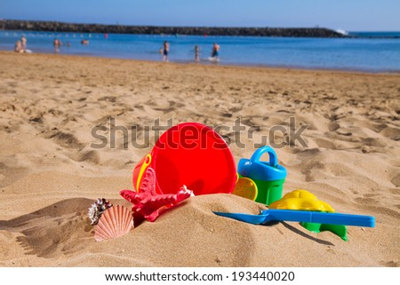 red bucket with plastic beach toys  in sand on sea shore at sunny summer day - stock photo