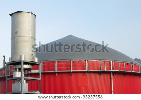 Red building of a bio gas plant in front of a blue sky