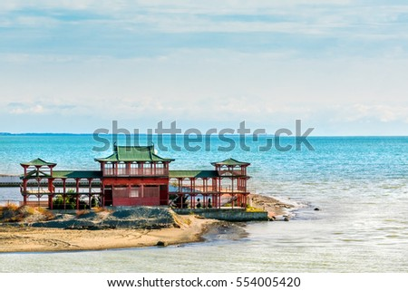 Red building with green tile roof on the beach