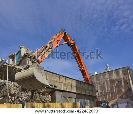 Red bulldozer destroying old building at a construction site - stock photo