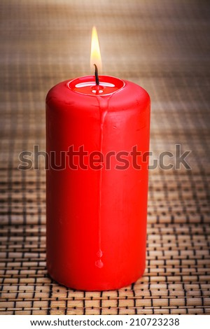 Red burning candle standing on wooden table. - stock photo