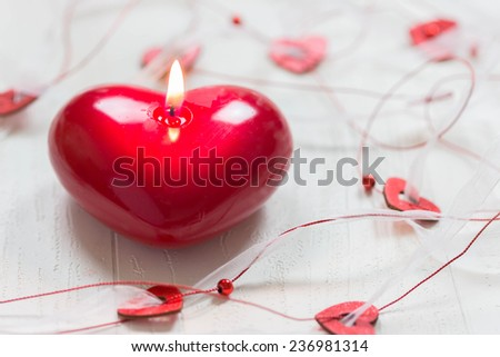 Red burning heart shaped candle on white background. Selective focus,Valentine - stock photo