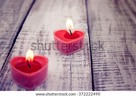 Red burning heart shaped candles on rustic white wooden table. Valentine's Day and Mother's Day background. Toned image. Soft focus. - stock photo