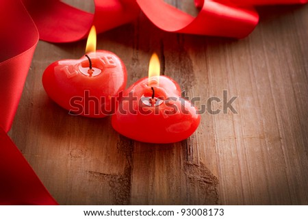 Red burning heart shaped candles over wood background. Valentine