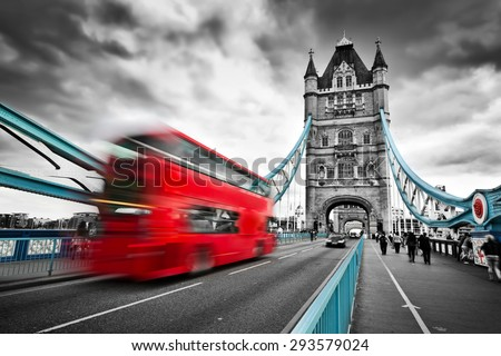 Red bus in motion on Tower Bridge in London, the UK. Dramatic rainy clouds. Black and white with red and blue bridge elements. - stock photo