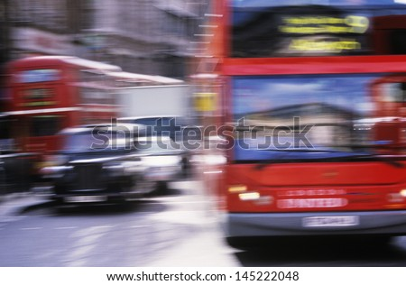 Red buses and black cabs on road in London motion blur - stock photo