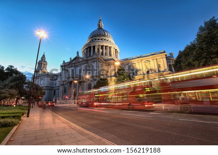 red buses passing Saint Paul's Cathedral in evening - stock photo