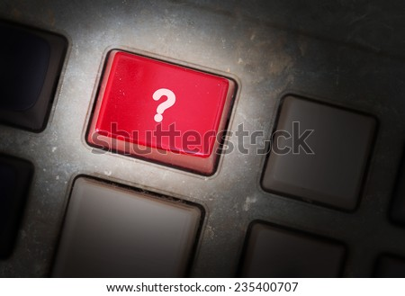 Red button on a dirty old panel, selective focus - question mark