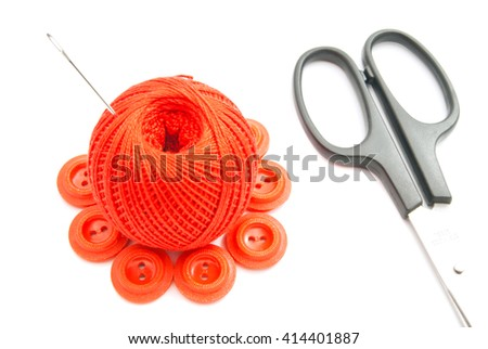 red buttons, needle, scissors and thread on white