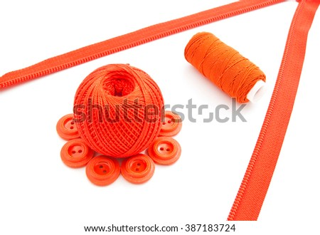 red buttons, zipper and thread on white background