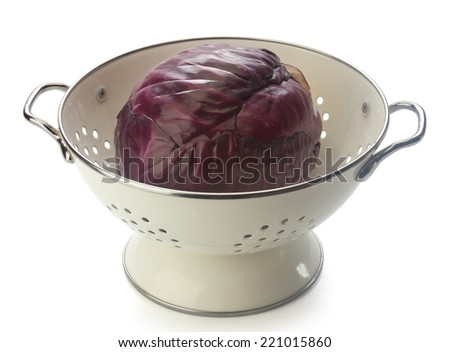 Red cabbage in the white enamel colander on the white background