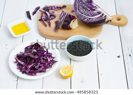 red cabbage salad ingredients with unpeeled sesame seeds and olive oil on white wood table
