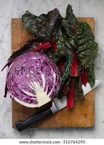 red cabbage with red silver beet leaves and kitchen knife on wooden chopping board, marble bench top - stock photo