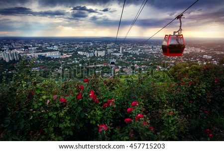 Red cabin of cable car and rose garden at city view at dramatic stormy sunset sky background