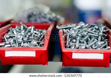 red cabinets with screws and bolts in a modern factory - stock photo