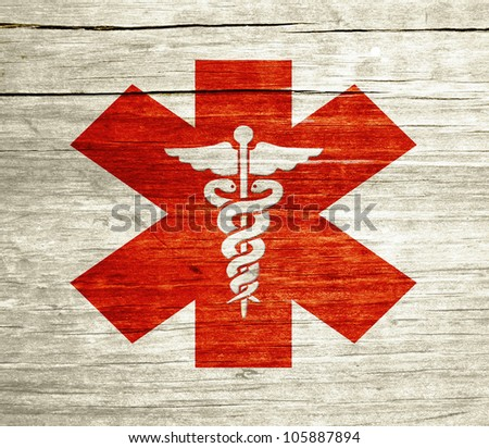 Red Caduceus on wood with grunge design - stock photo