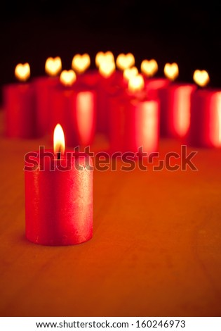 Red candle burning quietly, with similar candles on background with hearts for flames - symbol of season for peace and love