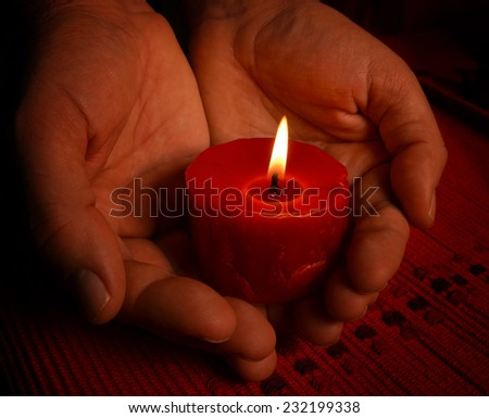 red candle hands in the dark - stock photo