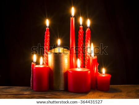 Red candle on dark background.