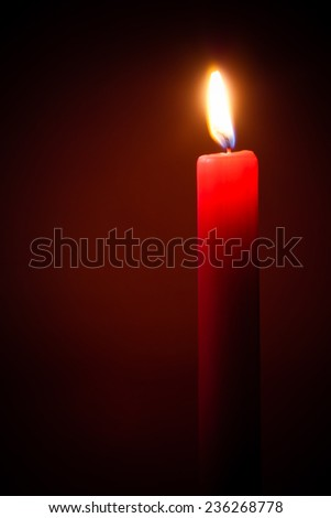 red candle on red background - stock photo