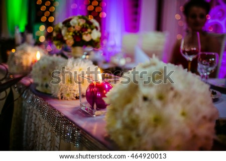 Red candle stands on the dinner table full of white bouquets