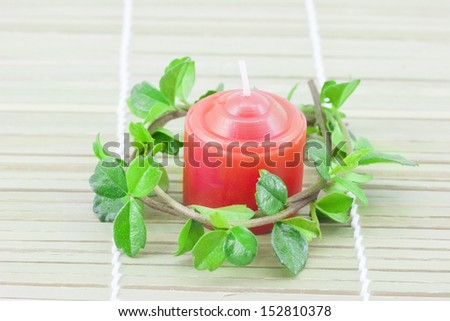 Red candle with a green on a bamboo mat