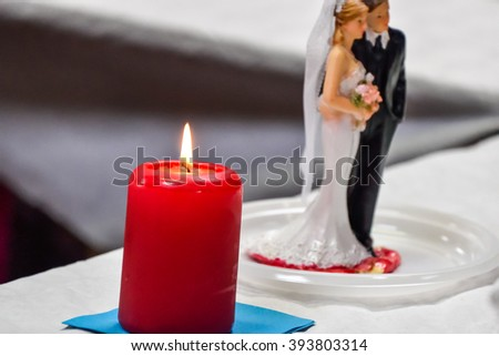 red candle with bride & groom doll on table. - stock photo